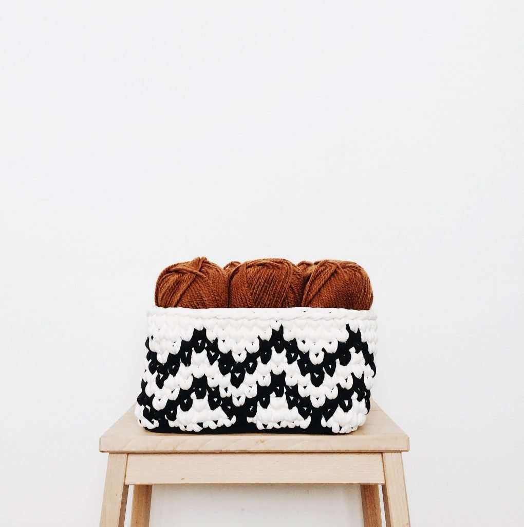 crochet basket with yarn in it sitting on a stool