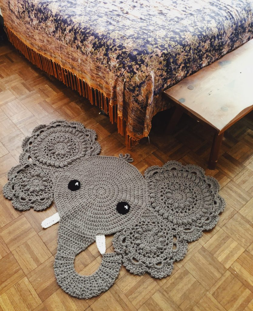 a bedroom with a corner of the bed showing and a crochet elephant rug on the floor