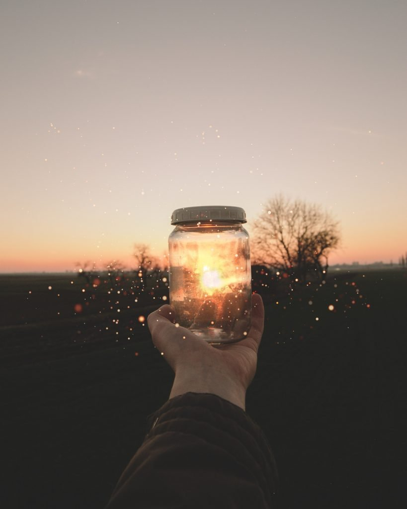 a hand holding a mason jar in front of a sunset with fireflies flying around it