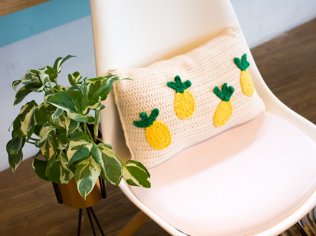 a white crochet pillow with pineapples on it sitting on a chair with a plant next to it
