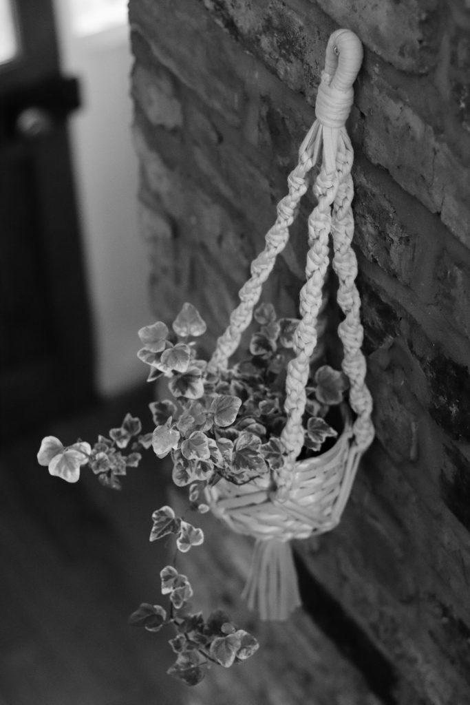 crochet plant hanger hanging on a brick wall