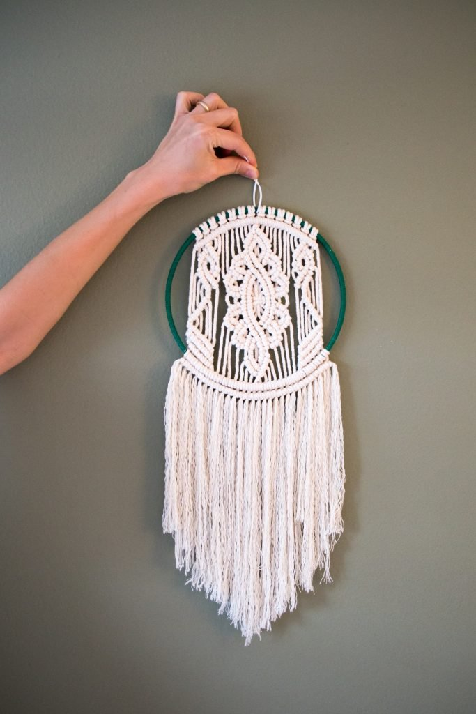 a hand holding a crochet wall hanging attached to a ring placed in front of a wall