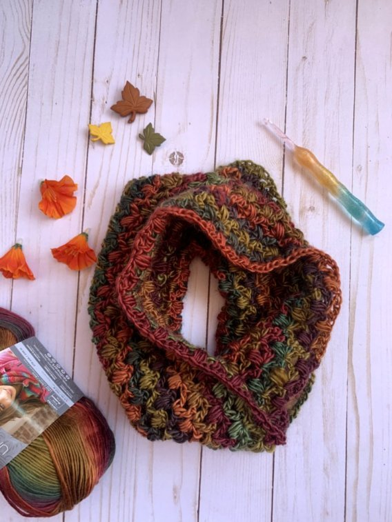A cowl in fall fashion colors with leaf decorations , crochet hook, and skein of yarn around it.