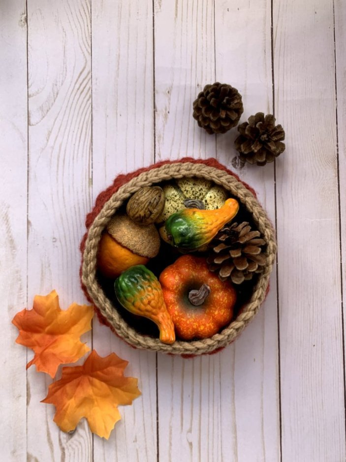 crochet basket filled with pumpkins, gourds, pinecones with 2 pinecones and 2 leaves on either side of it.