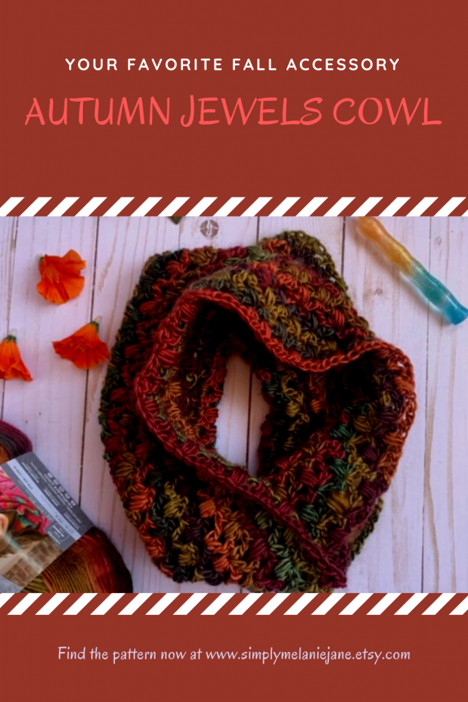 An autumn crochet cowl laid in a circle with a crochet hook, orange flowers, and yarn in the background.