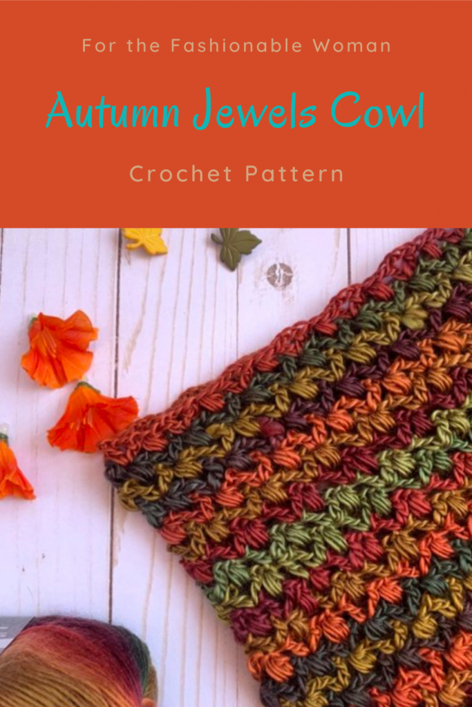 Pinterest Pin with a flat lay of of an autumn colored crochet cowl with leaf buttons, orange flowers and a skein of yarn in the background.