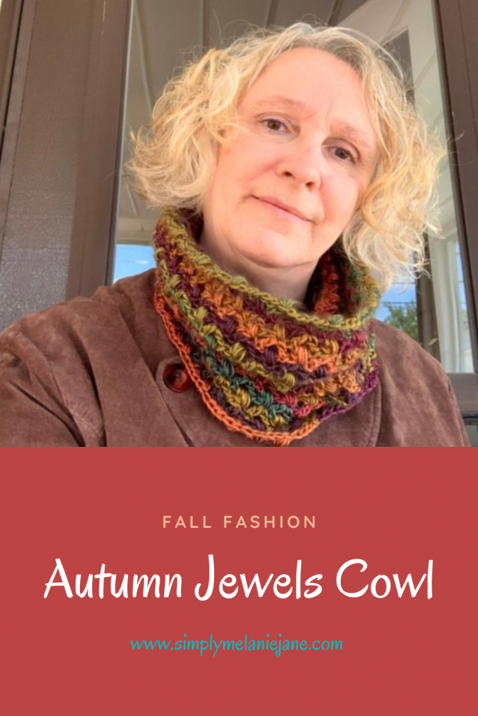 A pinterest pin of a blond woman slightly smiling wearing an autumn colored crochet cowl atop a brown jacket.
