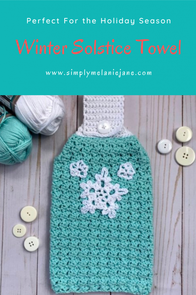 Winter cozy kitchen towel in aqua and wihite with snowflake decorations. White buttons and yarn in the background.