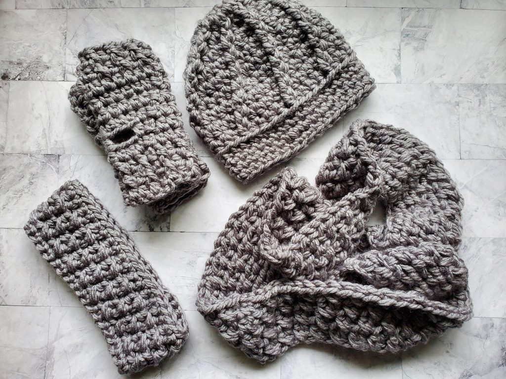 A gray set including hat, ear warmer, scarf and fingerless gloves.