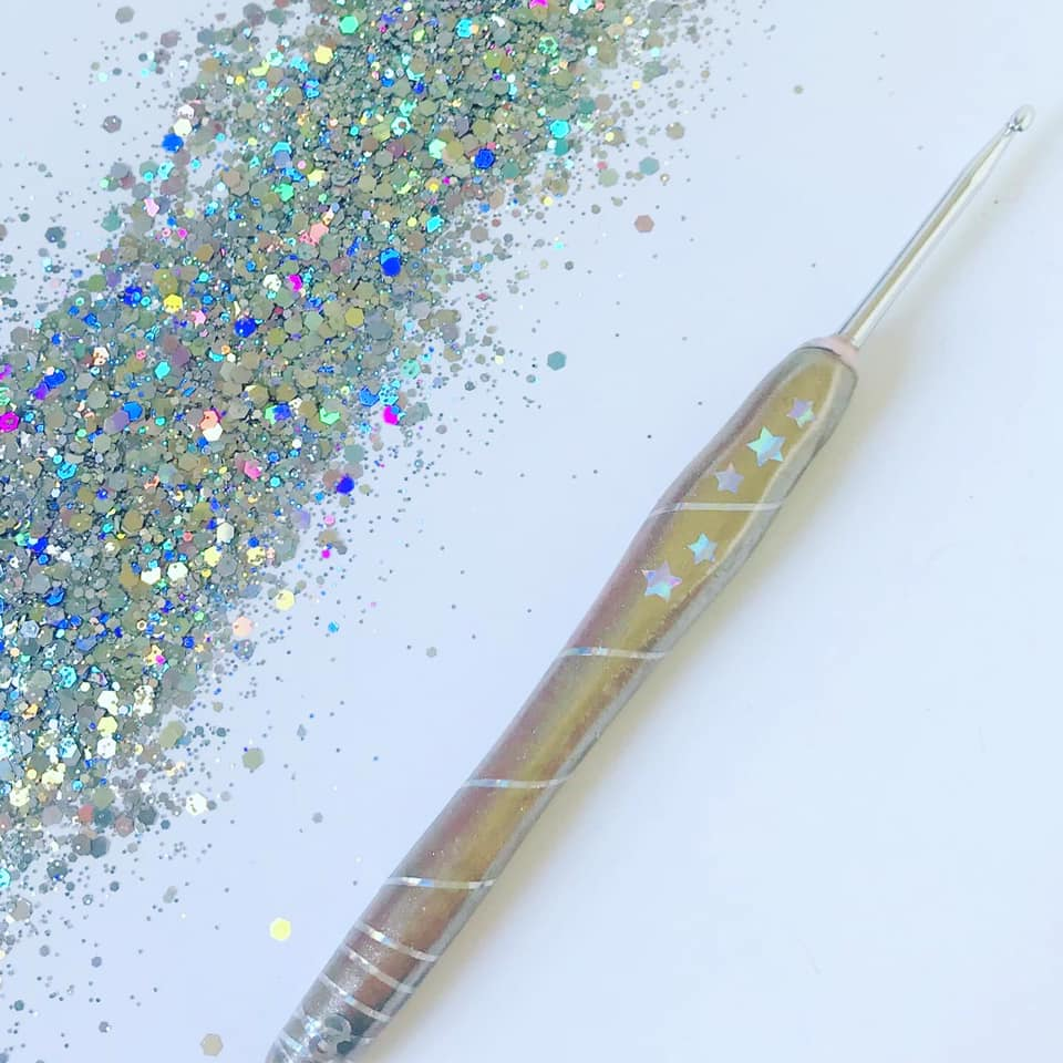 A handmade holographic, ergonomic crochet hook with stars and spirals on the base with a pile of glitter sitting beside it.