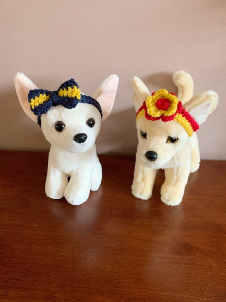 Two stuffed dogs, one is wearing a bow headband and the other is wearing a flower headband.