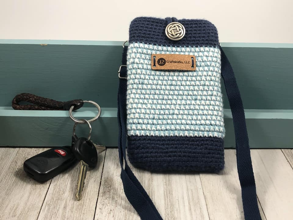 A crossbody cellphone bag in light blue and navy with a set of car keys nearby.