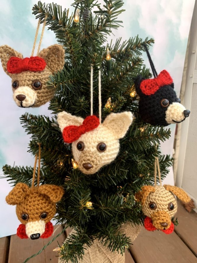 A small christmas tree with several different colored handmade dog ornaments hanging on it.