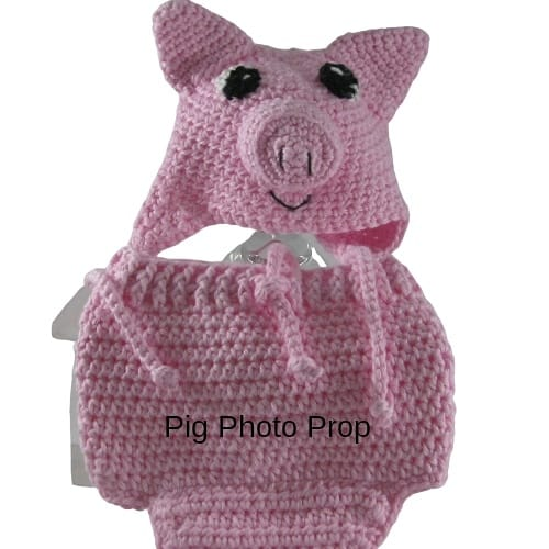A handmade pink pig hat and diaper cover photo prop for a baby.