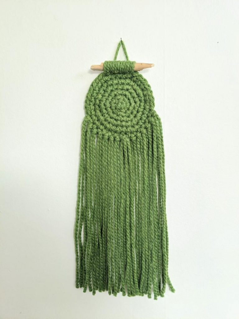 A handmade green circle crocheted wall hanging with a small stick and long fringe.