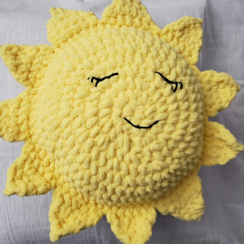 A  crocheted yellow sun pillow with embroidered sleeping eyes and mouth.