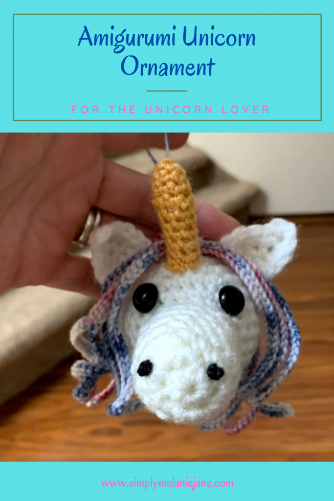 Pinterest Pin of a hand holding a white unicorn ornament with golden horn, black eyes, and blue/pink mane.
