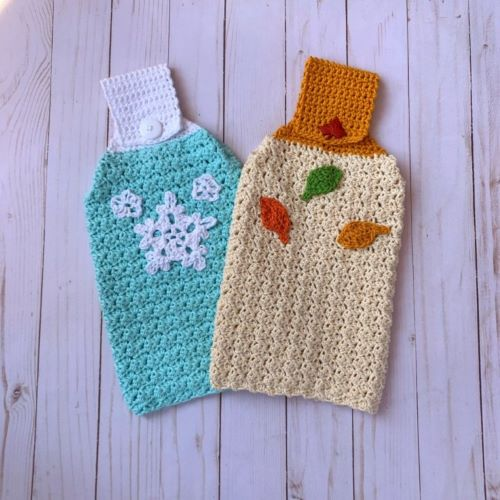 Two crochet hanging towels, one blue with snowflakes, one off white with autumn leaves.