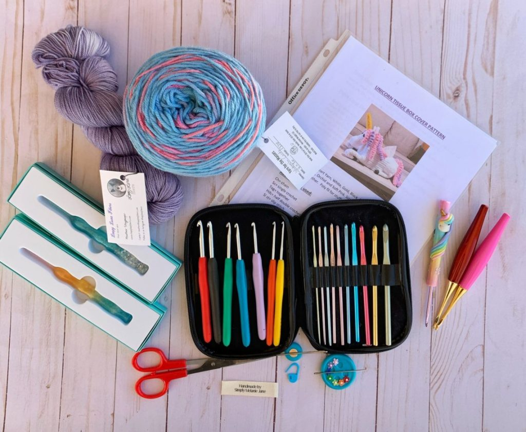 A picture of various crochet tools including yarn, crochet hooks, scissors, stitch markers, and needles.