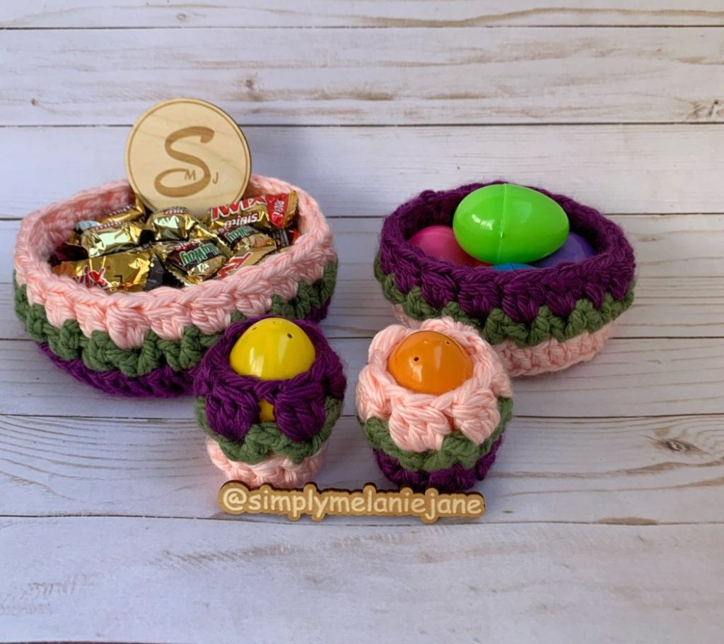 Two crochet flower baskets in pink and purple and two egg cups with the same colors.