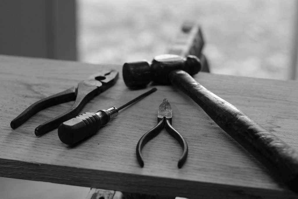 A black and white picture of a hammer, screwdriver, needle nose pliers, and regular pliers laying on a piece of wood.