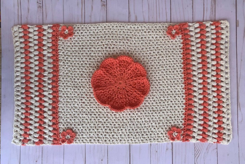 A flat lay of the crochet table runner made in cream and coral colors. A big coral flower is in the center with 4 smaller flowers on each corner.
