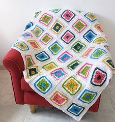 A white crochet blanket with colorful granny squares spread across a red chair.