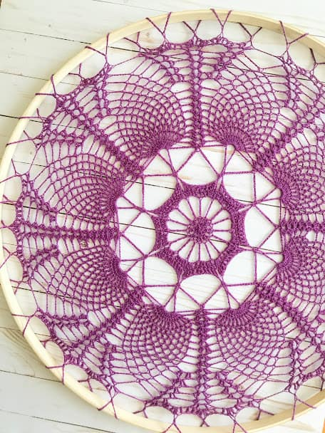 An intricate purple mandala design on a wooden circle gives off the spring home décor vibe.