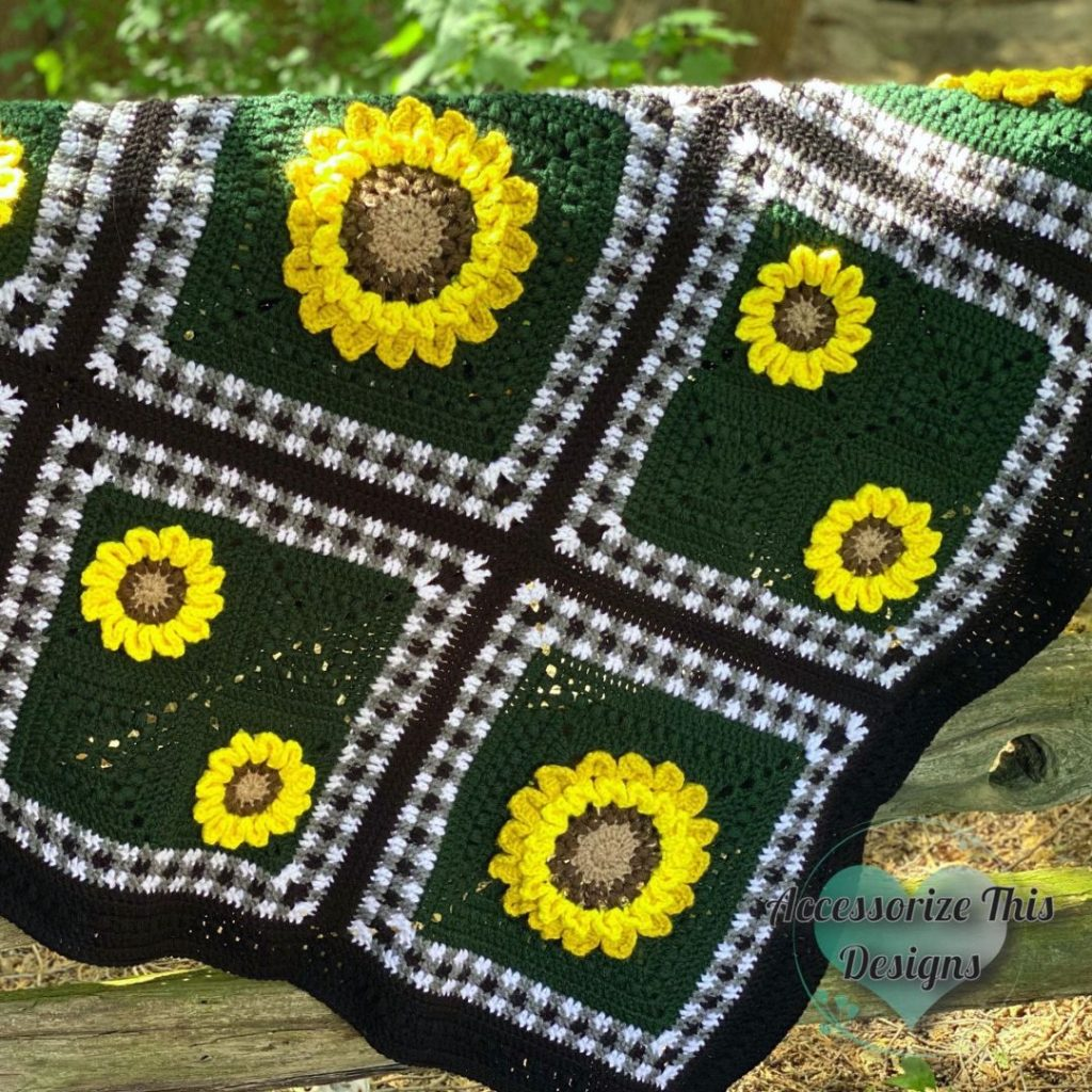 A sunflower crochet blanket hanging outside to brighten your spring home décor.