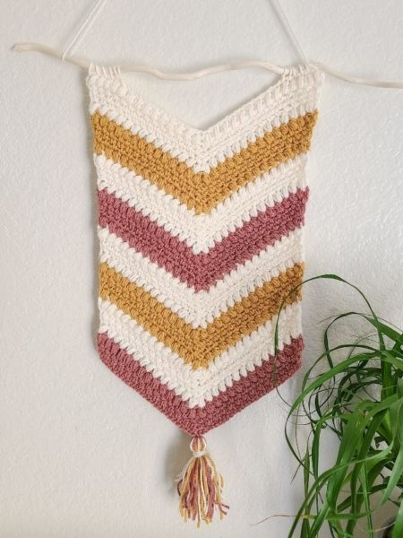 A V shaped crochet wall hanging in striped colors of cream, mustard, and mauve is a wonderful spring home décor design.