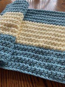 A blue and cream crochet blanket folded on a wooden floor.