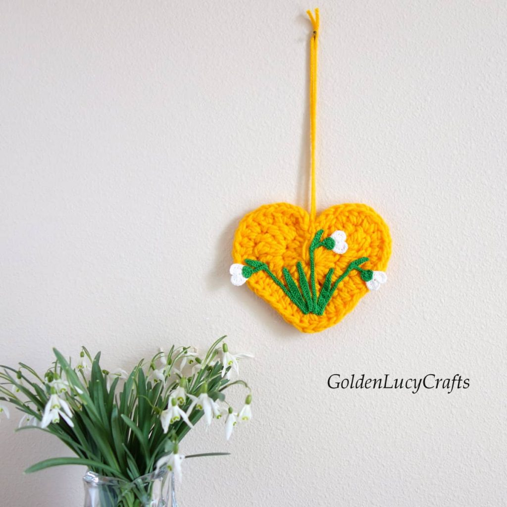 A yellow crochet heart with white spring flowers in the middle hanging on a wall. A vase of the same flowers sits nearby.