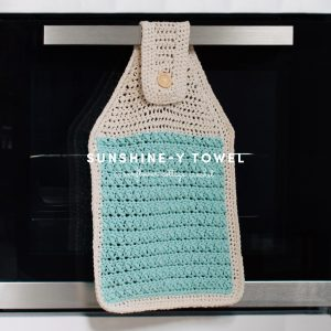 A white and blue crochet towel hangs on the handle of an oven.
