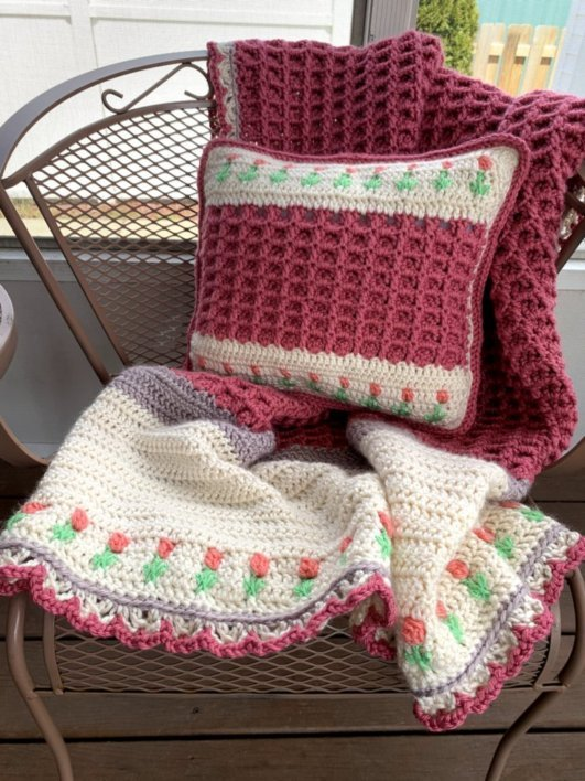 A crochet pillow and blanket with a tulip design sitting on a metal scrollwork chair.