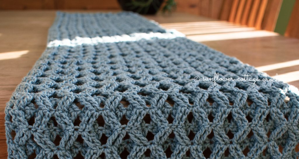 A gray textured table runner laid upon a wooden table for your dining spring home decor.