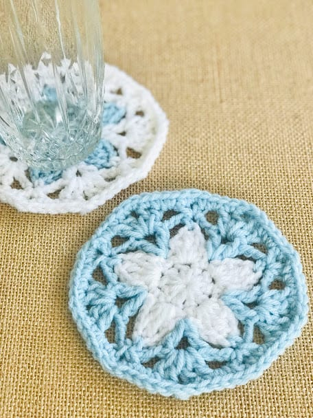 Blue crochet coaster with a white star shaped flower in the middle. A glass is sitting on a second coaster nearby.