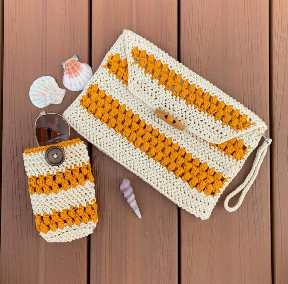 Crochet clutch bag and sunglasses case in ecru and gold laying on a wood deck. Sunglasses are peeking out of the case. Seashells are laying nearby.
