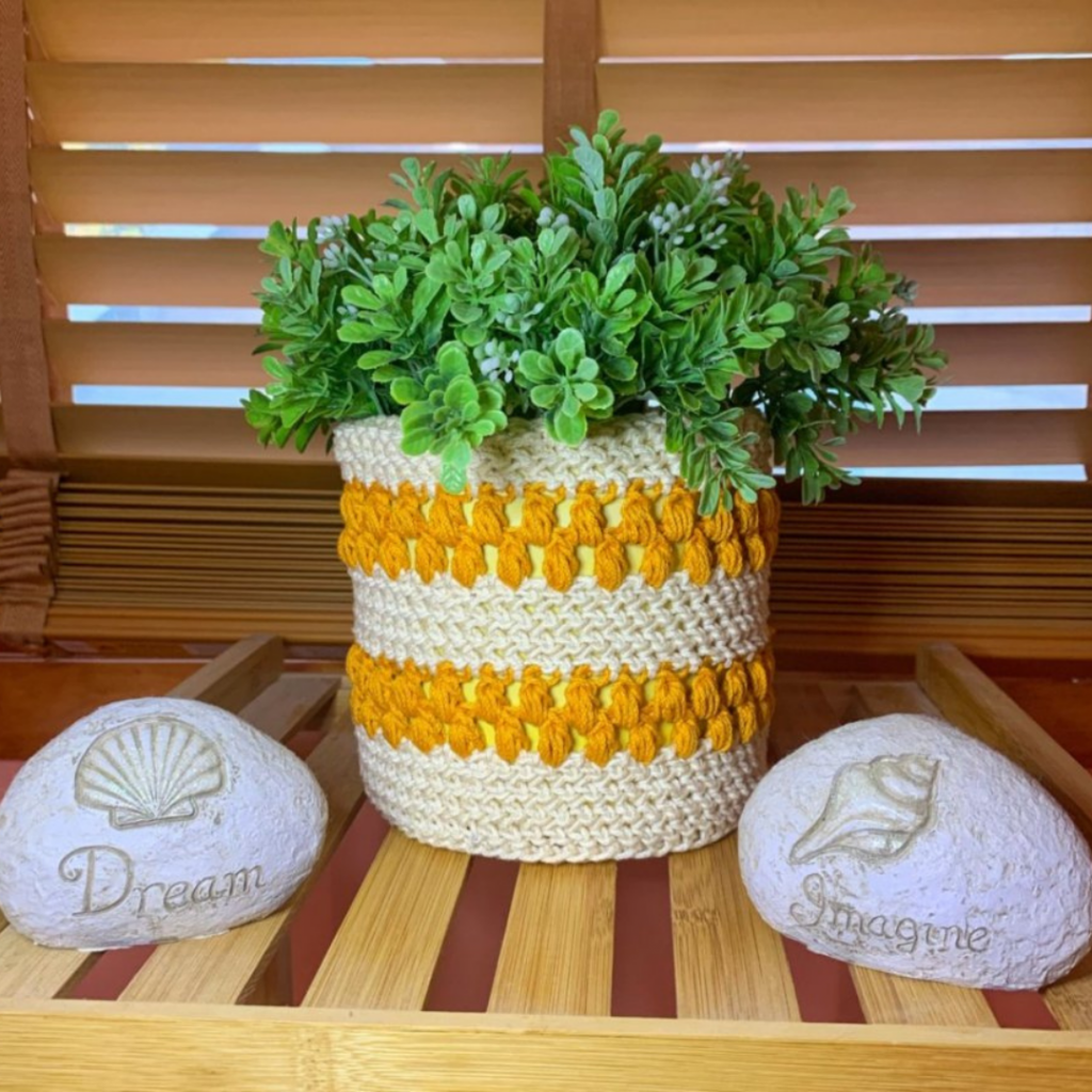 """Ecru and gold crochet plant cozy with green plant inside sits on a slatted table with two stones on either side that say """"Dream"""" and """"Imagine"""""""