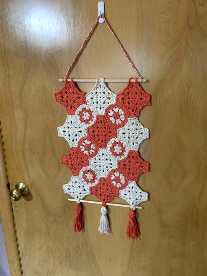 Coral and Cream Granny Square Wall Hanging on a brown stained door.