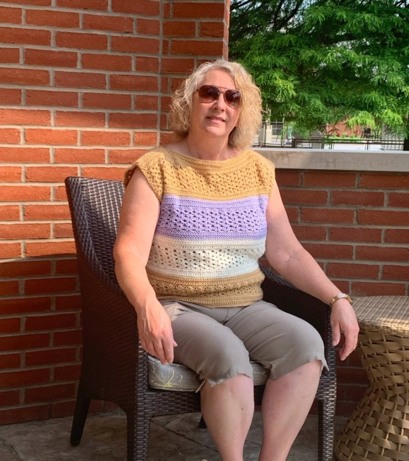 A woman sitting in a wicker chair in front of a brick building wearing the Layla Jane Crochet Top in color blocks of tan, purple, cream, and tan again.
