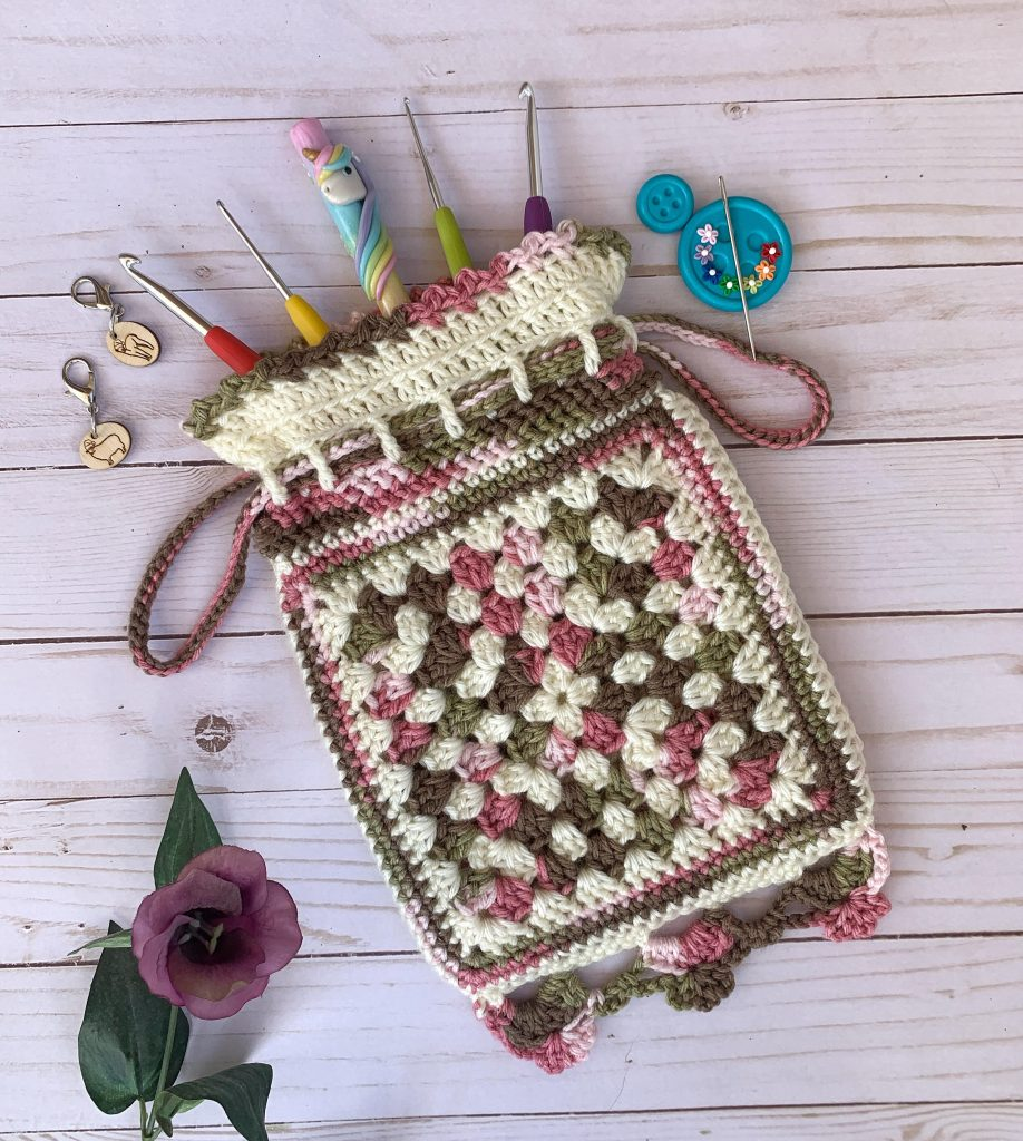 A crochet pouch using pink and green granny squares lays flat on a light wood background with crochet hooks half in and half out of bag. A purple flower, wooden stitch markers, and a blue needle minder sit close by.