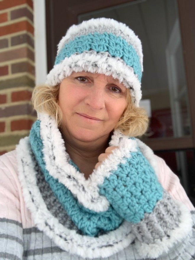 A blond haired woman wearing a teal crochet ear warmer, cowl, and fingerless gloves all with gray faux fur trim.