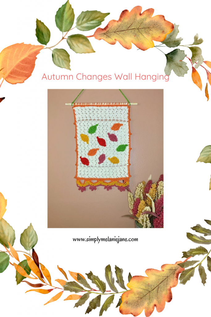 A Pinterest pin of an Autumn Wall Hanging with leaves, which hangs on a coco colored wall.
